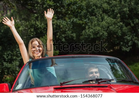 Happy woman having fun in red classy cabriolet while her boyfriend driving - stock photo