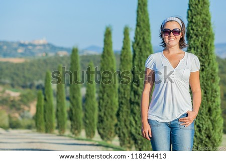 Happy woman having fun on vacations in Tuscan against cypress alley background - stock photo