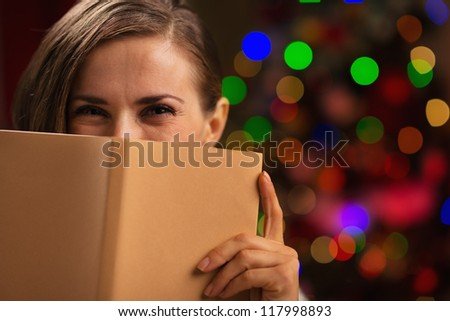 Happy woman hiding behind book in front of Christmas lights - stock photo