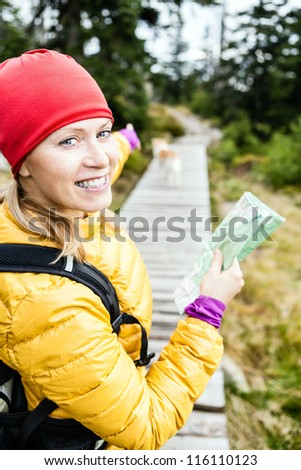Happy woman hiking and reading map in forest, hiker with dog, Karkonosze Mountains in Poland. Young female backpacker walking with canine. Trekking and travel in wilderness. - stock photo