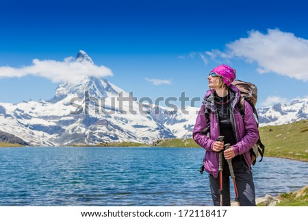 Happy Woman hiking in the mountains, walking and backpacking  - stock photo