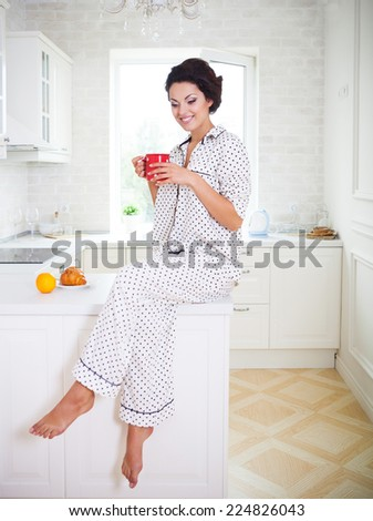 Happy woman holding a cup of coffee in her kitchen wearing pajamas - stock photo