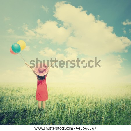 Happy Woman holding balloons  in green grass fields with clouds sky.Summer holiday concept.Vintage Tone. - stock photo