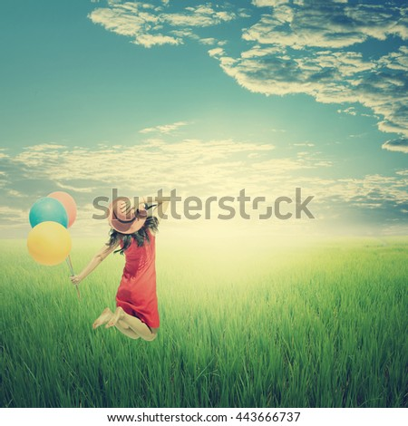 Happy woman holding balloons in yellow rice field and cloud sky.Summer holiday concept.Vintage Tone. - stock photo