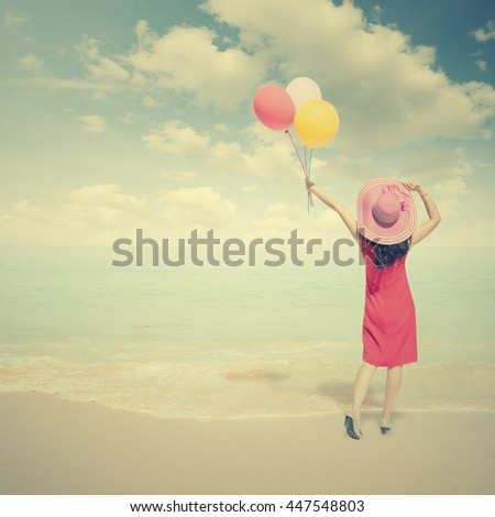Happy Woman holding balloons on the beach and clouds sky.Summer holiday concept.Vintage tone. - stock photo