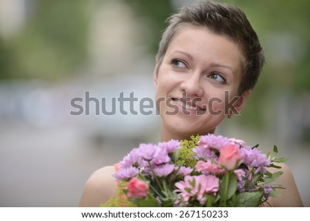Happy woman holding bunch of flowers in spring - stock photo