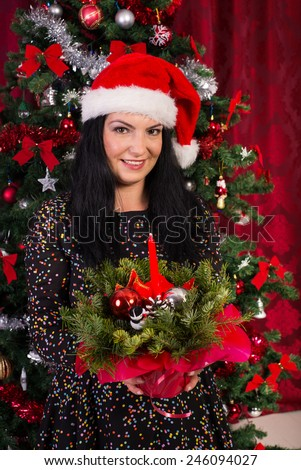 Happy woman holding Christmas red  arrangement with balls,pine cone , poinsettia and candle - stock photo