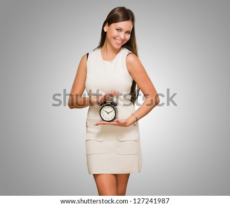 Happy Woman Holding Clock against a grey background - stock photo