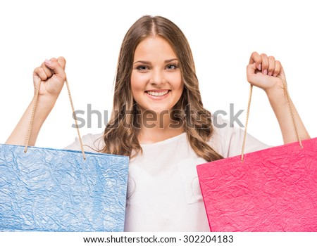 Happy woman holding colored shopping bags in two hands on white background. - stock photo