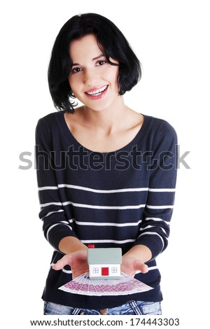 Happy woman holding euros bills and house model over white - real estate loan concept  - stock photo