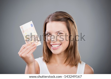 Happy woman holding fifty Euros over the grey background - stock photo