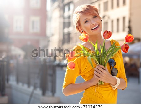 Happy woman holding flowers - stock photo