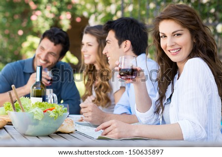 Happy Woman Holding Glass Of Wine With His Friends In Background - stock photo
