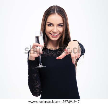 Happy woman holding glass with champagne and pointing finger at camera isolated on a white background - stock photo