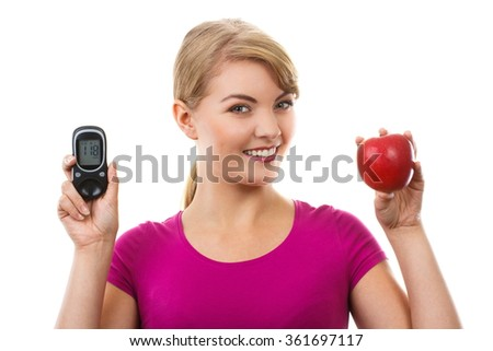 Happy woman holding glucose meter with positive result of measurement sugar level and fresh ripe apple, concept of diabetes, checking sugar level - stock photo