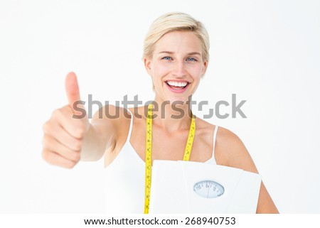 Happy woman holding scales with thumbs up on white background - stock photo