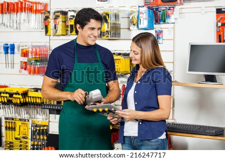 Happy woman holding screwdriver set with worker swiping credit card at hardware store - stock photo