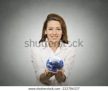 Happy woman holding showing glowing earth globe in her hands on grey wall background. Earth image provided by Nasa. Positive face expressions, emotions. Ecology, peace, eco friendly technology concept - stock photo