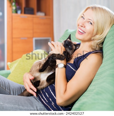 Happy woman holding Siamese kitten in arms and smiling - stock photo