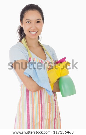 Happy woman holding spray bottle and rag in apron and rubber gloves - stock photo