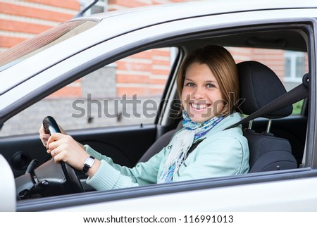 Happy woman holding steering wheel sitting in car - stock photo