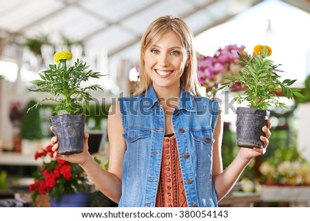 Happy woman holding two flowers (tagetes) in her hand - stock photo