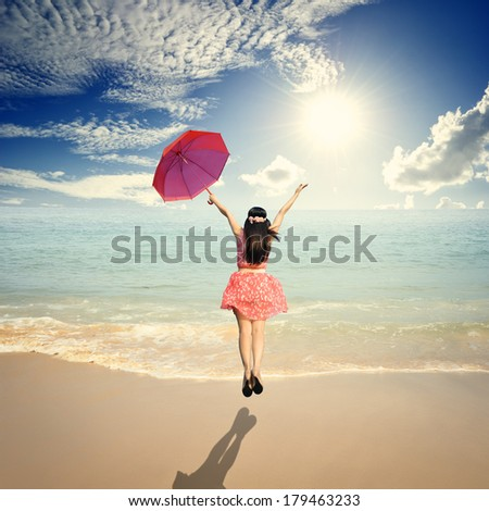 Happy Woman holding umbrella and Jumping in Sea sun sky - stock photo