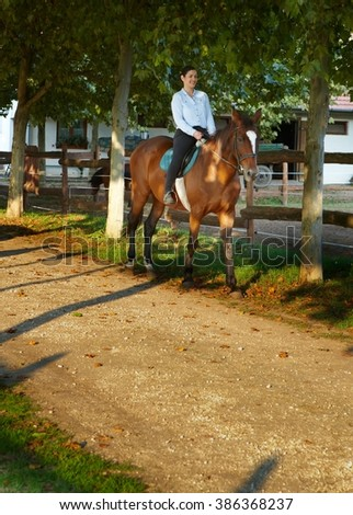 Happy woman horseback riding at farm. - stock photo