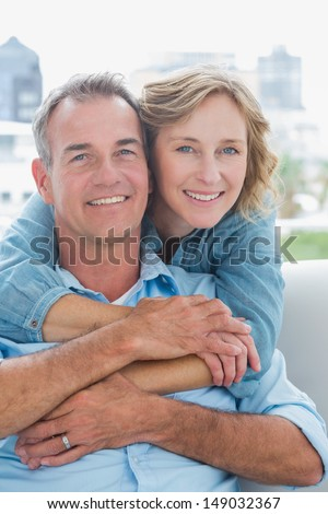 Happy woman hugging her husband on the couch from behind at home in the living room - stock photo