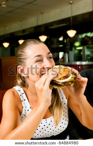 Happy woman in a fast food restaurant eating a hamburger and seems to enjoy it - stock photo
