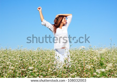 Happy woman in beauty field with white flowers - stock photo