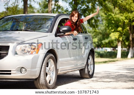 Happy woman in car waving out the window - stock photo