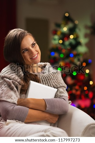 Happy woman in chair in front of Christmas tree hugging tablet PC - stock photo