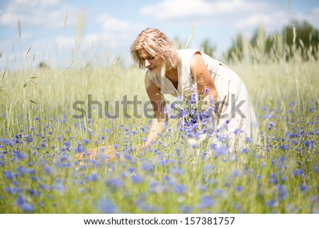Happy woman in corn field with cornflowers - stock photo