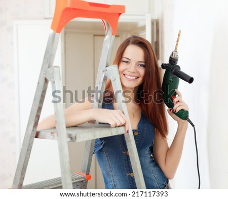 Happy woman in dungarees with drill near stepladder in interior - stock photo
