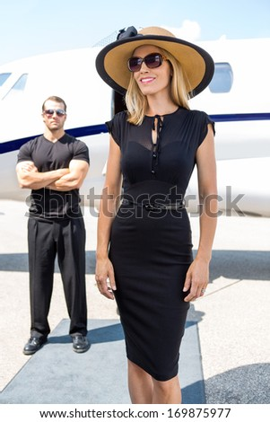 Happy woman in elegant dress with bodyguard and private jet in background - stock photo