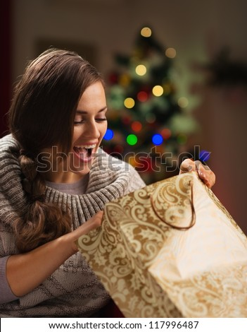 Happy woman in front of Christmas tree looking in shopping bag - stock photo