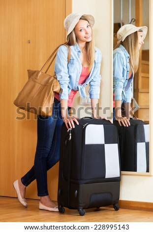 Happy woman in hat with a suitcase going on holidays - stock photo