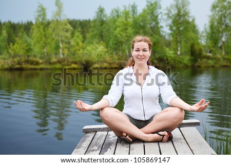 Happy woman in lotos pose sitting on wooden boards on lake edge. Copyspace - stock photo