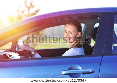 Happy woman in new blue car - stock photo