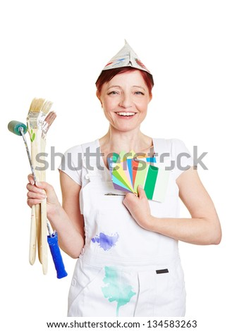 Happy woman in painter overall with brushes and color fan - stock photo