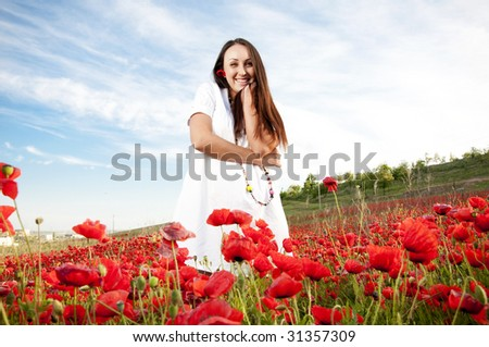 Happy woman in poppy flowers - stock photo