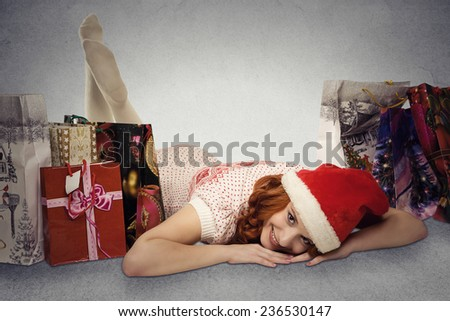 Happy woman in red santa claus hat with christmas gifts dreaming fun holidays. Young girl looking up smiling with shopping bags isolated grey wall background with copy space. Positive face expression - stock photo