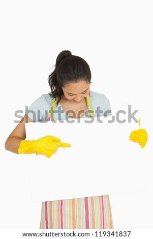 Happy woman in rubber gloves and apron pointing to white surface she is holding - stock photo
