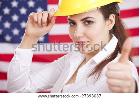 happy woman in safety helmet with thumb up gesture - american flag in background - stock photo
