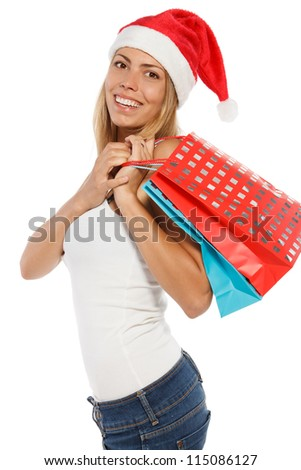 Happy woman in Santa hat holding shopping bags, over a white background. - stock photo