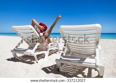 Happy woman in Santa Helper Hat lie on sunbed and showing  thumbs up at caribbean sandy beach   - stock photo