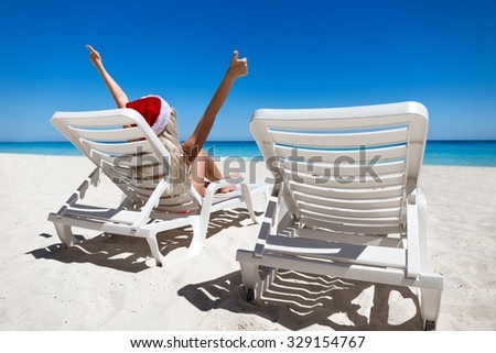 Happy woman in Santa Helper Hat lie on sunbed with outstretched hands showing  thumbs up at caribbean sandy beach   - stock photo