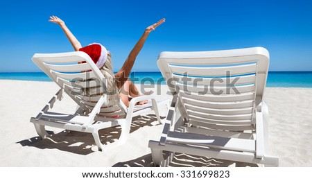 Happy woman in Santa Helper Hat sitting on sunbed with outstretched hands at caribbean sandy beach 