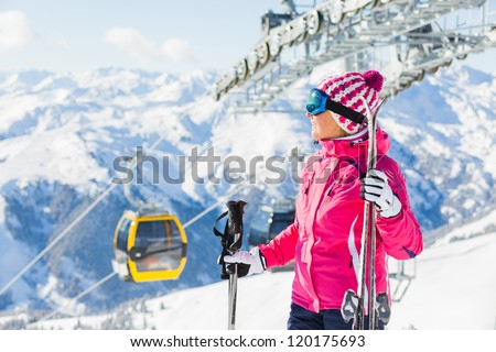 Happy woman in ski goggles against a ski-lift and wonderful winter mountains backgroundagainst wonderful winter mountains background and , Zellertal, Austria - stock photo